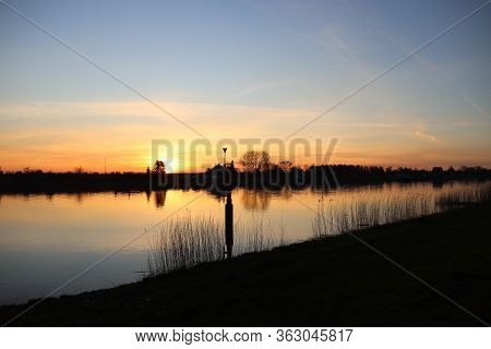 The Sun Rises Over The Water Of The River Hollandsche Ijssel Near The Dike At Park Hitland