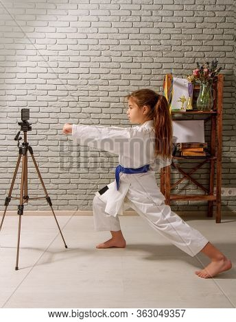 A Little Girl In A White Kimono With A Blue Belt Takes Karate Lessons Via The Internet While At Home