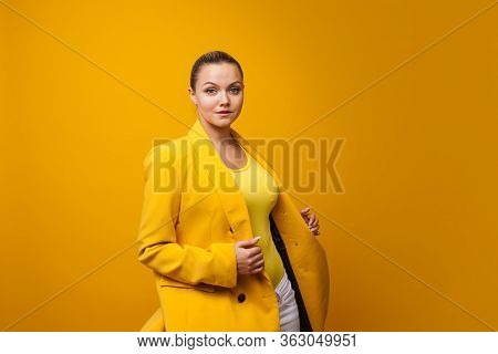 Stylish Positive Young Woman On Yellow Background, Copy Space. Studio Portrait Of A Girl In A Yellow