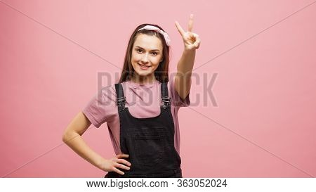 Cute Girl In Overalls Shows The Sign Of Two Fingers, Victory Sign, A Portrait On A Pink Background,