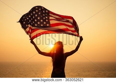 Woman Holding Usa Flag And Looking At Sunrice