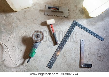 Cement Floor With Tools - Angle Grinder, Construction Rulers And Humer Are In The Apartment That Is