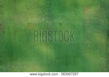 Green Painted Surface Of A Metal Gate Closeup. Texture With A Gradient Of Green On The Metal Surface