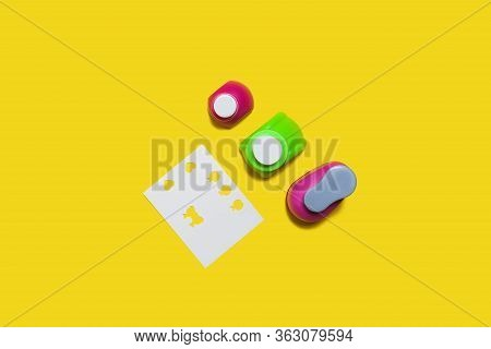Row Of Small Plastic Hole Punchers Near Sheet Of Paper Standing On The Yellow Background. Concept Of