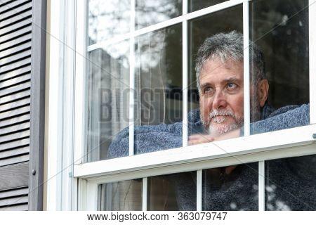 Senior man inside looking out window during quarantine