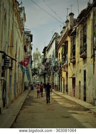 Cuban Street With Cuban People Walking And A Cuban Flag. At The End Of The Street There Is The Touri
