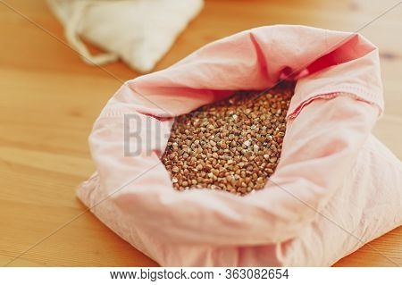 Organic Buckwheat Grain In Reusable Bag Close Up. Groceries In Reusable Textile Bags On Wooden Table