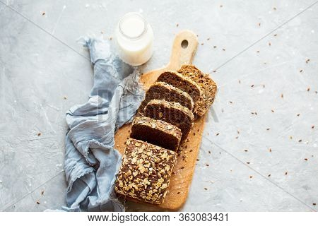 Sliced bread on a board with milk. Tasty, beautiful homemade bread with grains. Homemade baking. G