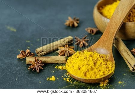 Colorful Turmeric Powder In Wooden Spoon, Star Anise And Cinnamon On The Dark Background Closeup. He