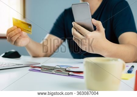 Young Man In Blue Casual Clothes Entering Security Code With Mobile Phone And Paying With Credit Car
