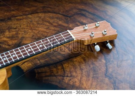 Close-up Of A Ukulele Fretboard - Small Light Brown Instrument On Beautiful Wooden Table.