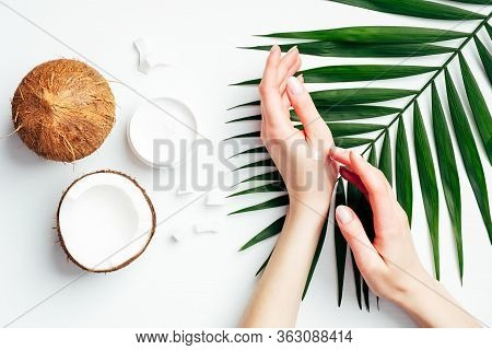 Coconut Oil Hand Cream, Organic Cosmetic For Skin Care Concept. Female Hands Applying Coconut Lotion