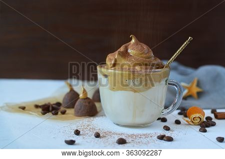 Cold Dalgon Coffee In Clear Glasses With Chocolate Candies, Coffee Grains, Orange Skins On A White B