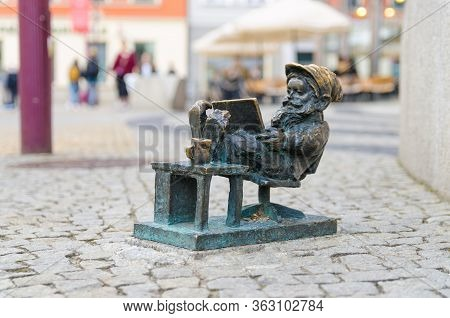 Wroclaw, Poland, May 7, 2019: Dwarf Is Sitting And Reading A Book, Famous Bronze Miniature Gnome Wit