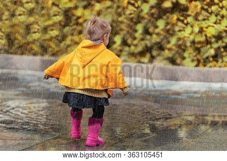 A Happy Little Girl In A Yellow Raincoat And Pink Rubber Boots Walking In The Rain On The Street Alo
