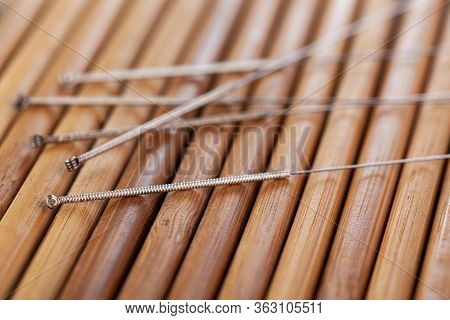 Table With Needles For Acupuncture. Silver Needles For Traditional Chinese Acupuncture Medicine On A