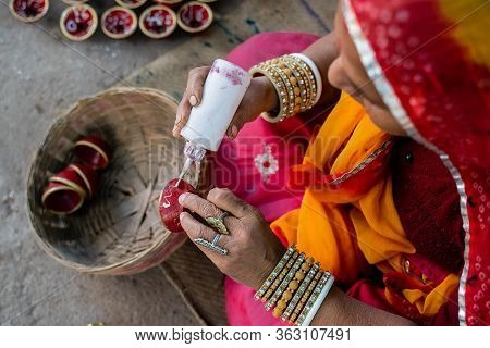 Indian Woman In Traditional Costume And Bangles Decorating And Painting A Small Clay Bowl