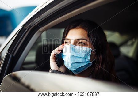 Woman Wearing A Medical Sterile Mask In A Taxi Car On A Backseat Looking Out Of Window Talking On Th