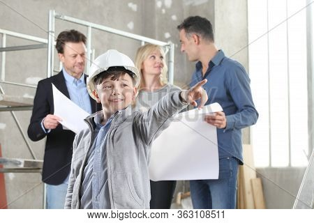 Architect Showing House Design Plans To A Family With Child Pointing His Finger As House Building Go