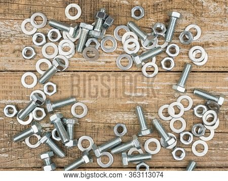 Fastening Elements On A Wooden Background. The View From The Top. The Bolts And Nuts.