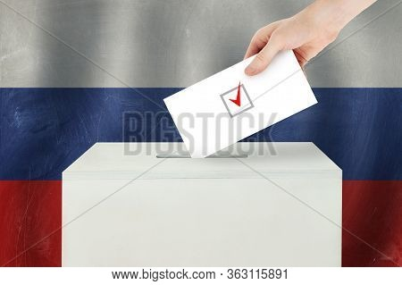 Russian Vote Concept. Voter Hand Holding Ballot Paper For Election Vote On Polling Station