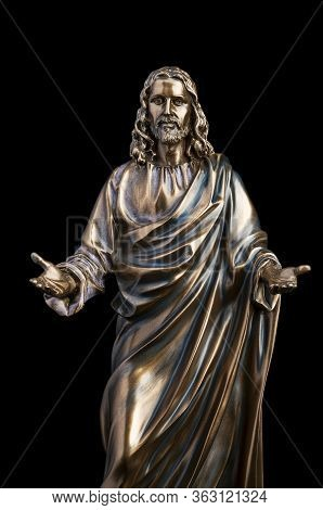 A Bronze Statue Of A Jesus Christ Isolated On Black