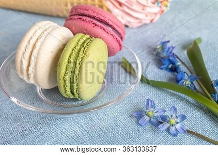 White, Purple And Pistachio Macaroons On A Transparent Saucer And Blue Spring Flowers. Macarons Or M