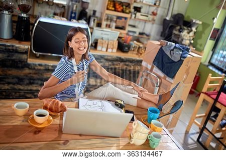 female watching content on her laptop, laughing , with her legs on the table. casual, relaxed, break, pause
