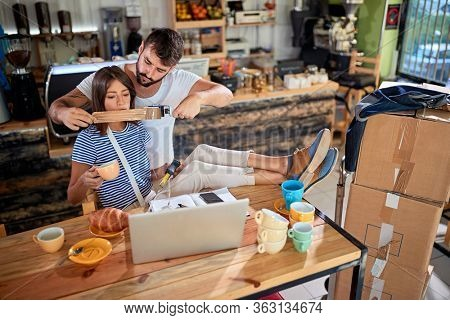 young man is putting a tape across woman's mouth, joking as she talk too much. young couple joking in new  unopened cafe of their own. Starting new bussines