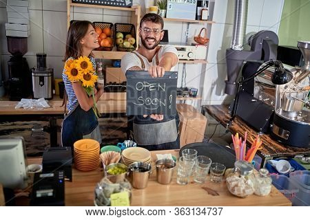 young couple is about to open their own cafe. opening, enthusiastic, excitement, joy, startup, business concept