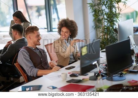 female colleague explaining idea to a male colleague gesturing at desk in modern open space office. casual modern business