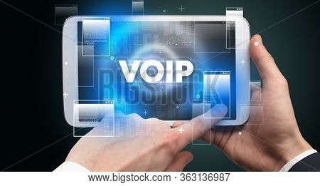 Close-up of a hand holding tablet with VOIP abbreviation, modern technology concept