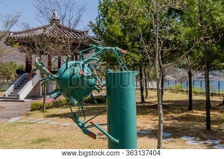 Jinan, South Korea; April 21, 2020: Iron Welded Sculpture Resembling A Virus With Oriental Pavilion
