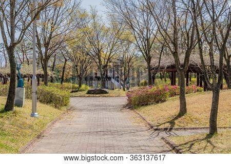 Jinan, South Korea; April 21, 2020: Walkway In Rural Park With Oriental Pavilions Behind Trees On Sp
