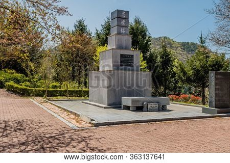 Jinan, South Korea; April 21, 2020: Tall Square Concrete Monument With Chinese Characters On Top.