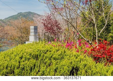 Jinan, South Korea; April 21, 2020: Tall Square Structure Behind Lush Green Bush And Red And Purple