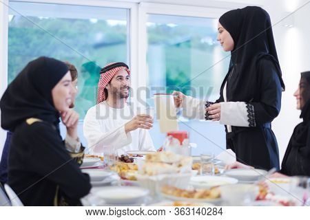 Eid Mubarak Muslim family having Iftar dinner drinking water to break feast. Eating traditional food during Ramadan feasting month at home. The Islamic Halal Eating and Drinking