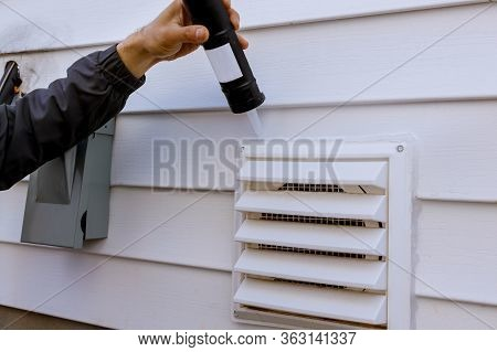 Dryer Exhaust Ventilation Fan On Side Of House With Plastic White Trim With Silicone