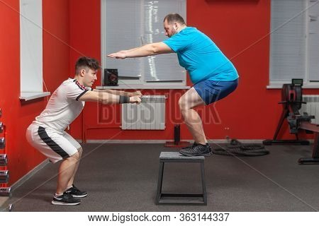 Eager Overweight Man Is Doing Jumping In The Gym Under The Guidance Of A Personal Trainer