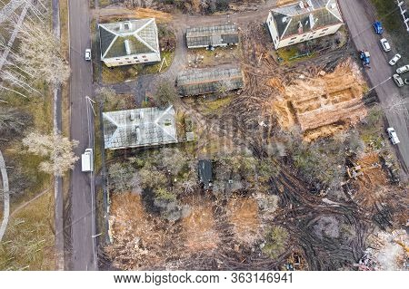 Heavy Excavator Working At Demolition Site In Ruins Of Old Buildings. Aerial Drone Photo Looking Dow