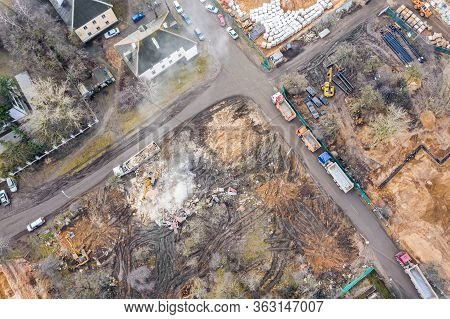 Heavy Construction Machines Clearing Out Pile Of Debris Of Destroyed Building After Demolition. Aeri