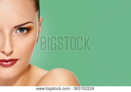 Beautiful Face Of Young Adult Woman With Clean Fresh Skin On Background Emerald Shade Green Color