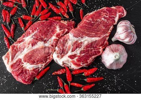 Raw Pork Meat. Fresh Steaks On Slate Board On Black Background. Garlic And Peper. Top View
