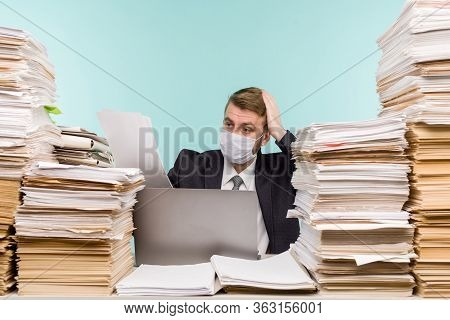 A Male Accountant Or Company Manager Works In An Office In A Pandemic In View Of The Accumulated Pap