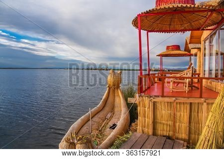 Uros Floating Island And Totora Traditional Boat On Titicaca Lake Near Puno City, Peru