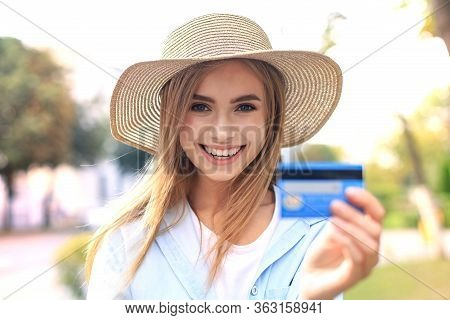 Cheerful Young Optimistic Girl Standing Outdoors, Holding Credit Card In Hand.