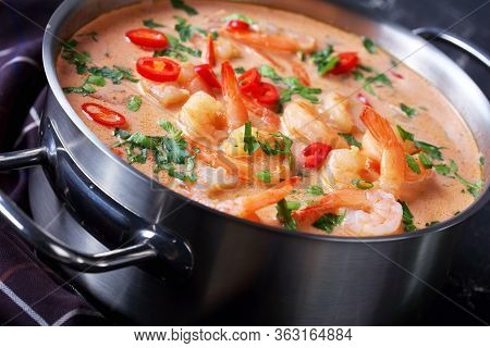 Close-up Of Tom Yum Soup, Tom Kha Soup In A Saucepan On A Concrete Table With Brown Cloth