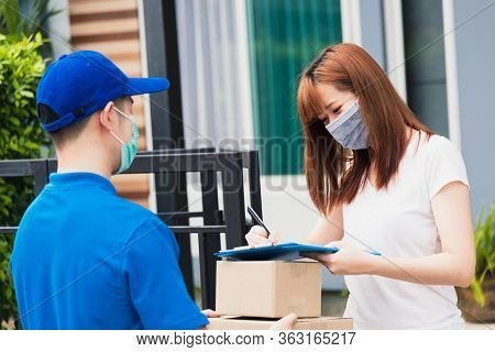Asian Young Delivery Man With Package Post Boxed He Protective Face Mask Service Woman Customer Usin
