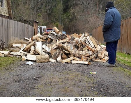 A Man Standing Next To A Woodpile Just Unloaded On The Street, Outdoor Shot
