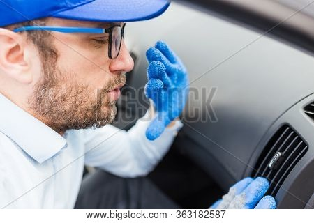 Car Maintenance Worker Feeling Bad Smell From Air Conditioning System. Car Reparation Concept.